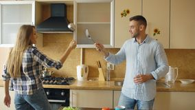 Attractive couple having fun in the kitchen fencing with ladle and spoon while cooking breakfast at home Stock Images
