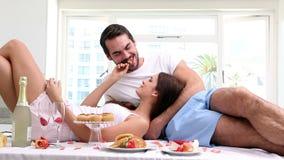 Attractive couple having an indulgent breakfast stock video