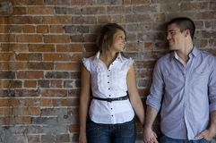 Attractive couple hold hands. In front of a brick wall Stock Photo
