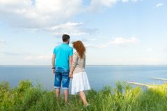 Attractive couple holding each other in hand and looking at lake and blue sky with clouds stock image