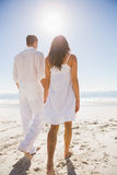 Attractive couple holding hands and walking to the water Royalty Free Stock Photography