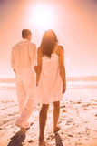 Attractive couple holding hands and walking to the water. At the beach Royalty Free Stock Image