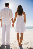 Attractive couple holding hands and watching the water Royalty Free Stock Photography
