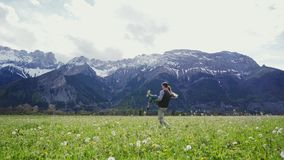 Attractive couple holding by hands and whirling on mountain meadow in Alps. Distant plan. 4k stock video footage
