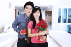 Attractive couple holds a gift and flowers Stock Image