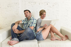 Attractive couple at home couch happy woman internet addict on digital tablet ignoring sad husband Royalty Free Stock Images