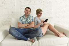 Attractive couple at home couch happy woman internet addict on mobile phone ignoring sad husband Stock Photo