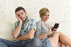 Attractive couple at home couch happy woman internet addict on mobile phone ignoring sad husband Royalty Free Stock Photography