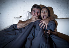 Attractive couple at home enjoying watching television horror movie covering with blanket Stock Photo