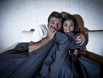 Attractive couple at home enjoying watching television horror movie covering with blanket Stock Images
