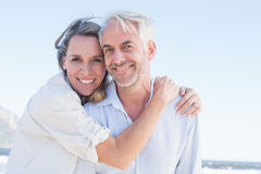 Attractive couple hugging at the beach smiling at camera Royalty Free Stock Photography