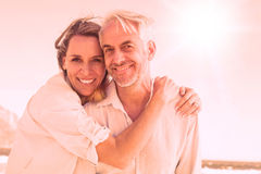 Attractive couple hugging at the beach smiling at camera Stock Image