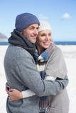 Attractive couple hugging on the beach in warm clothing Royalty Free Stock Image