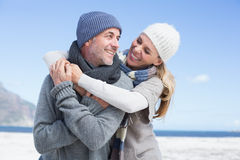 Attractive couple hugging on the beach in warm clothing Royalty Free Stock Images