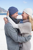 Attractive couple hugging on the beach in warm clothing Stock Photography