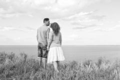 Attractive couple hugging in the field and looking at lake and blue sky with clouds at sunset royalty free stock photography