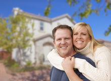 Attractive Couple Hugging In Front of House Royalty Free Stock Photo