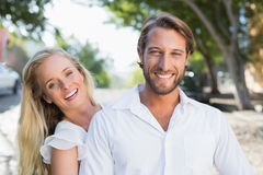 Attractive couple hugging and smiling at camera Stock Photos