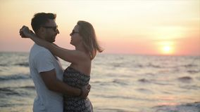 Attractive Couple Hugging During Sunset Near the Ocean. Honeymoon Vacation Concept. Attractive Couple Hugging During Sunset Near the Ocean. Honeymoon Vacation stock video footage