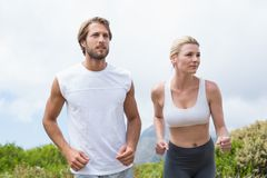Attractive couple jogging on mountain trail Royalty Free Stock Images