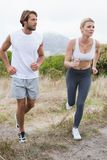 Attractive couple jogging on mountain trail Royalty Free Stock Photography