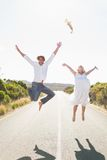 Attractive couple jumping with arms raised on the road Royalty Free Stock Images