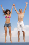 Attractive couple jumping outdoors Stock Photography