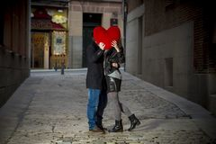 Attractive couple kissing with a red heart pillow Stock Image