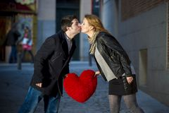 Attractive couple kissing with a red heart pillow Stock Photo