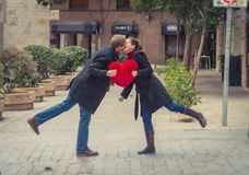 Attractive couple kissing with a red heart pillow Stock Photos