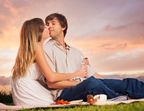Attractive couple kissing on romantic picnic. Attractive couple kissing on romantic sunset picnic Stock Image