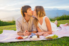 Attractive couple kissing on romantic picnic. Attractive couple kissing on romantic sunset picnic in countryside Royalty Free Stock Photos