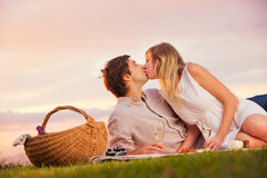 Attractive couple kissing on romantic picnic. Attractive couple kissing on romantic sunset picnic in countryside Royalty Free Stock Photography