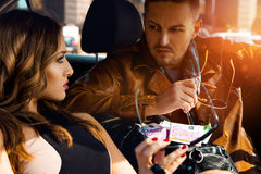 Attractive couple looking at each other in car with a bag full o Royalty Free Stock Photo
