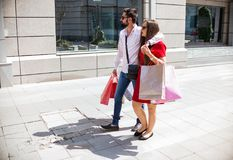 Attractive couple looking at shopping purchases on a sunny day. Beautiful young couple in love going on a shopping spree in the city on a sunny day Royalty Free Stock Image