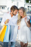 Attractive couple looking at shopping purchases. On a sunny day in the city stock photos