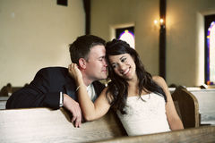 Attractive couple in love. Attractive bride and groom sitting in church pews snuggling and happy together Royalty Free Stock Photo