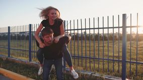 An attractive couple in love embrace and enjoy an intimate moment together, against the sunset or sunrise stock video footage