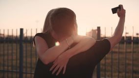 An attractive couple in love embrace and enjoy an intimate moment together, against the sunset or sunrise stock footage