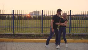 An attractive couple in love embrace and enjoy an intimate moment together, against the sunset or sunrise stock video
