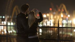 Attractive couple in love embrace and enjoy an intimate moment together at night, against the backdrop of port lights stock video