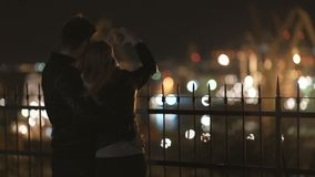 Attractive couple in love embrace and enjoy an intimate moment together at night, against the backdrop of port lights stock video footage