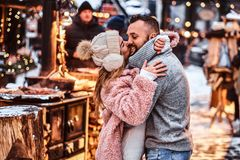Attractive couple in love, enjoying spending time together while embracing at the winter fair at a Christmas time. A cheerful attractive couple in love, enjoying royalty free stock photography