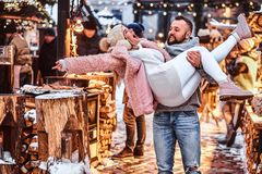 An attractive couple in love. A handsome man holding his girlfriend on hands, having fun together while standing at the. An attractive couple in love. A handsome royalty free stock photo