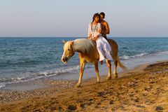 Attractive couple in love riding horse on the beach. Royalty Free Stock Image