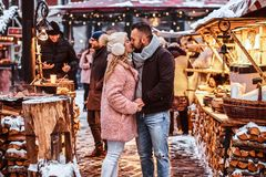 An attractive couple in love wearing stylish warm clothes holding hands and kissing while standing at the winter fair at. A happy couple in love wearing stylish royalty free stock images