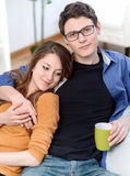 Attractive couple of lovers sitting on a sofa taking a hot drink Royalty Free Stock Photography