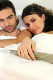 Attractive couple lying in bed Stock Photography