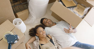 Attractive couple lying on the floor of their home Stock Images