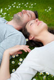 Attractive couple lying in grass at the park Stock Images